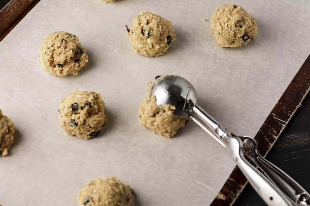 white chocolate chip cookie dough being scooped onto a baking sheet