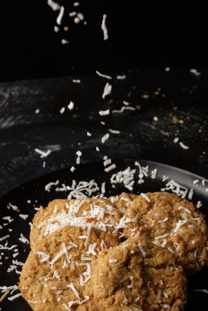 Coconut falling onto brown butter cookies