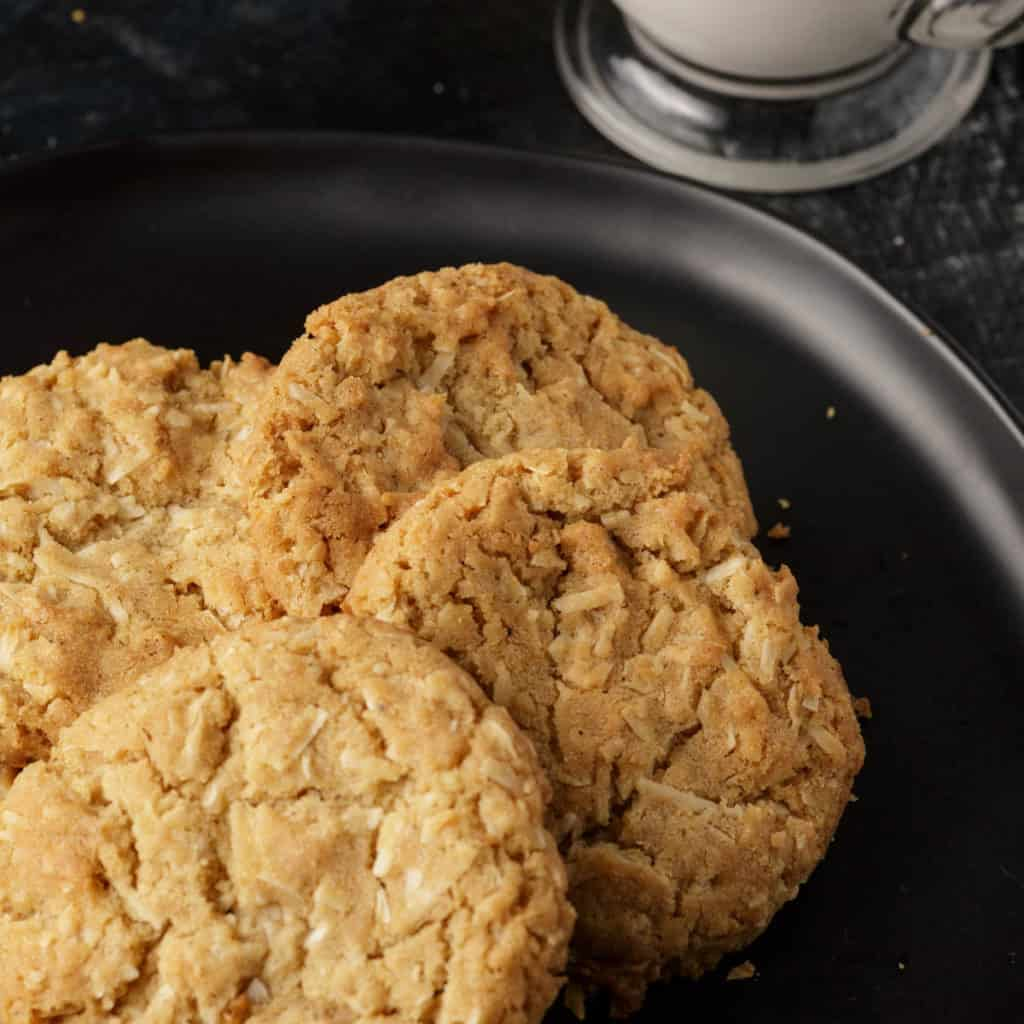 A plate of coconut brown butter cookies with a plate of milk