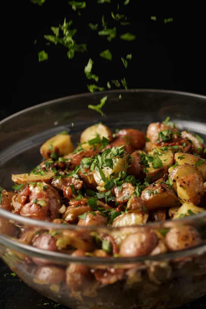 Parsley being sprinkled over warm potato salad