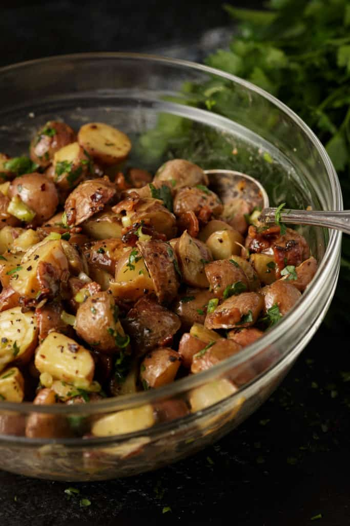 A glass bowl of roasted potato salad