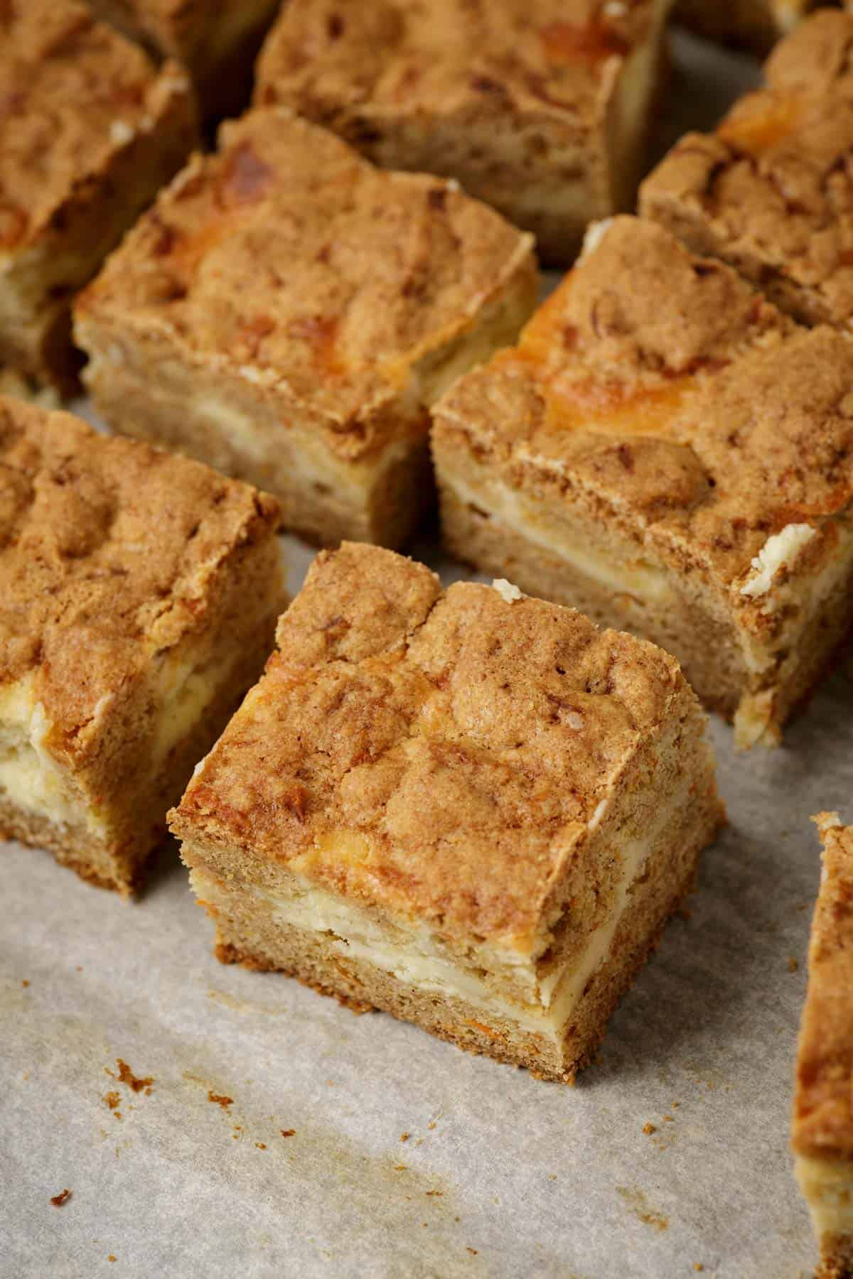 A batch of carrot cake cheesecake bars on parchment paper