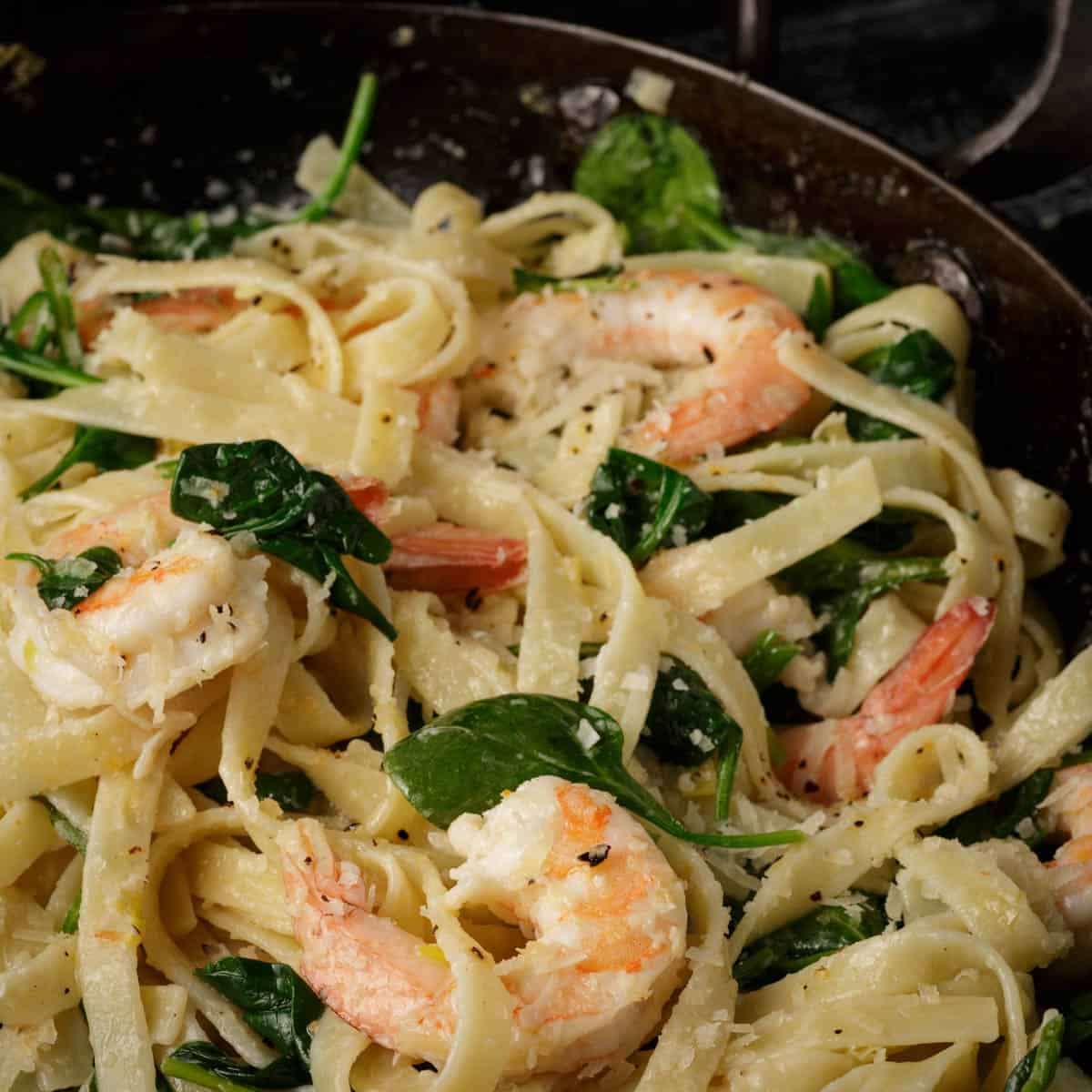 A skillet of shrimp and spinach pasta