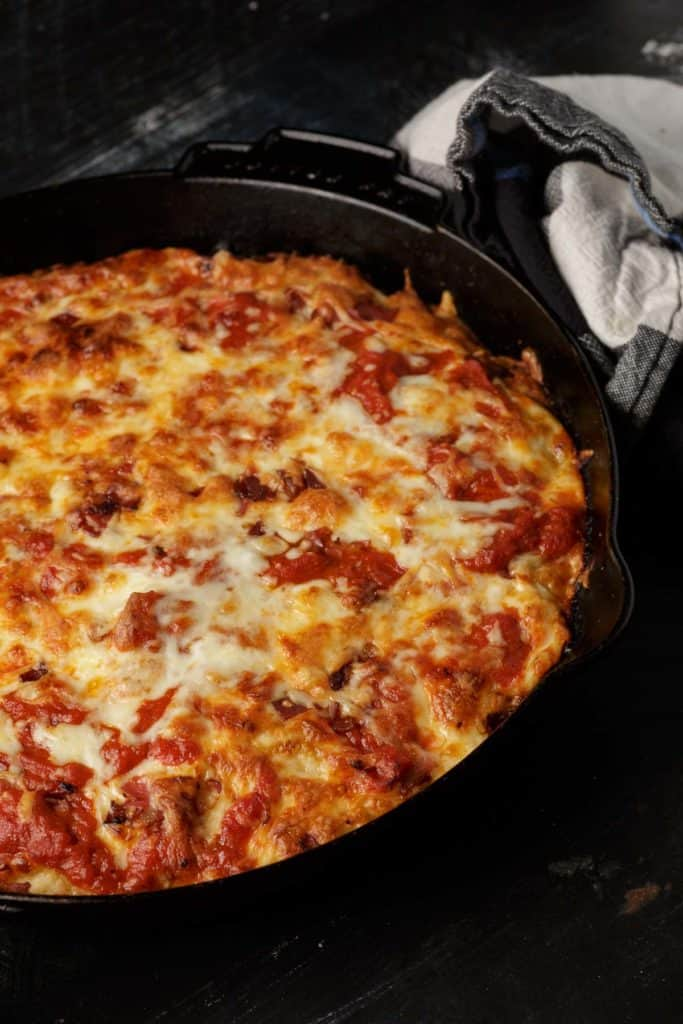 A cast iron skillet with homemade pizza dough
