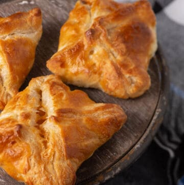 Three puff pastry pockets filled with sausage, eggs and apples