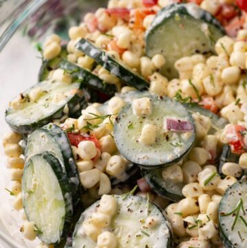 A glass bowl of corn and cucumber salad