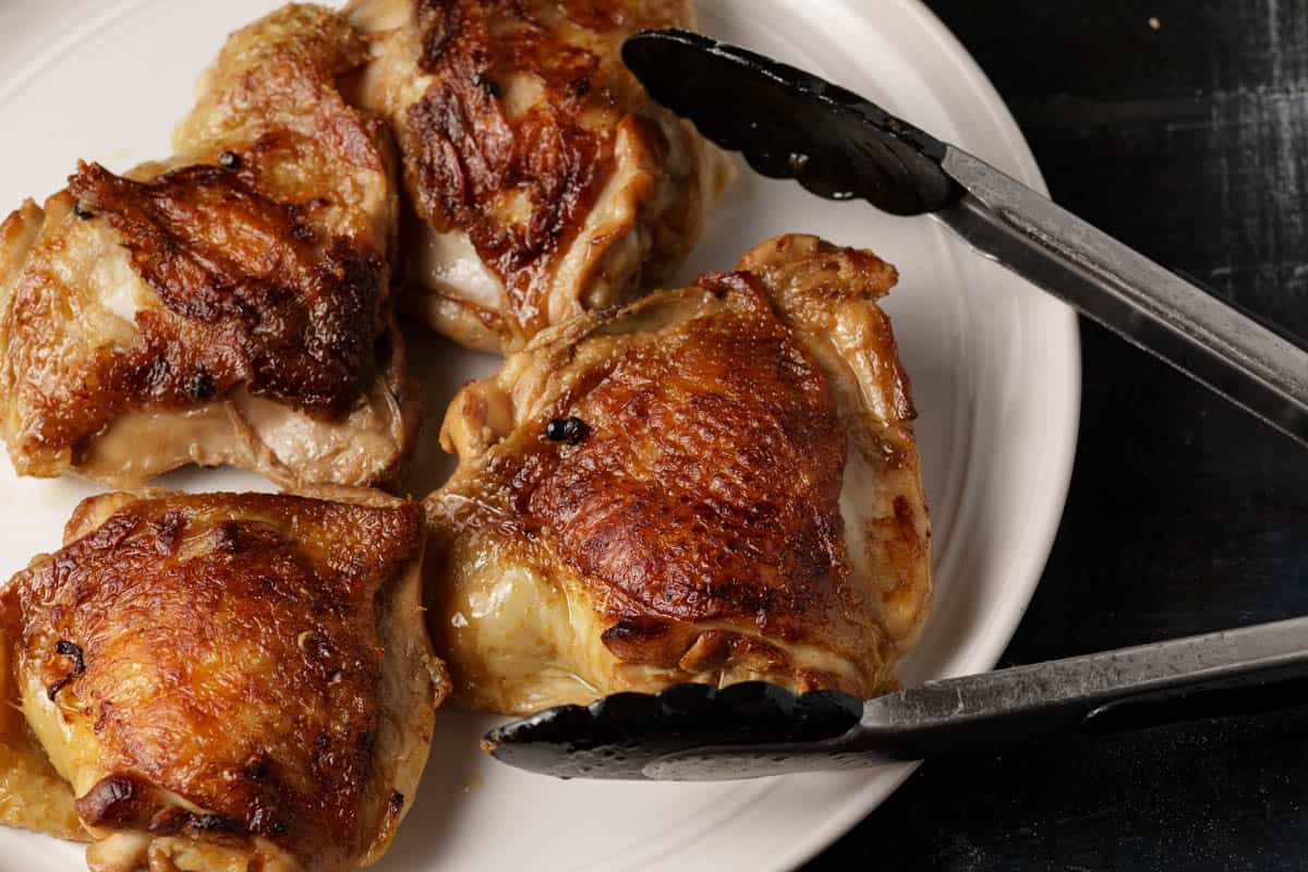 chicken thighs that have been browned on a white plate