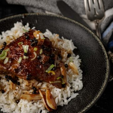 Chicken adobo on a bed of rice with a linen napkin