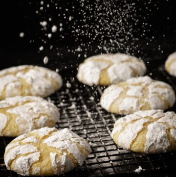 Lemon cookies on a rack with powdered sugar dropping