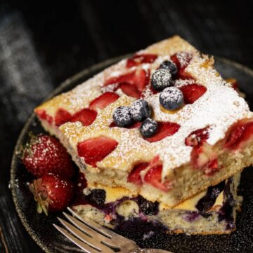 A serving of a sheetpan pancake with strawberries and blueberries
