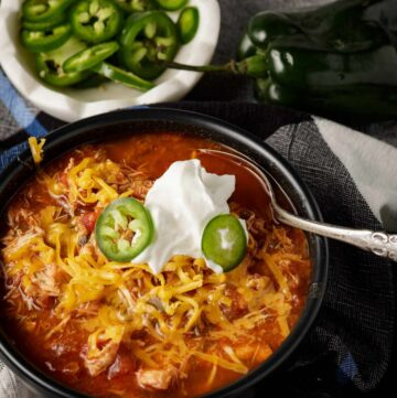 A bowl of chicken chili with sour cream