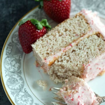 A slice of fresh strawberry cake with a bite on a fork