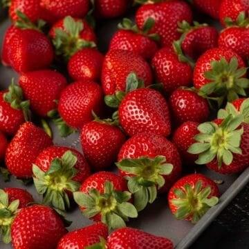 Fresh strawberries on a sheet pan for strawberry crostini