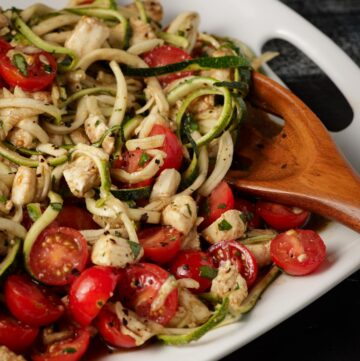 A white platter of zoodles mixed with tomatoes