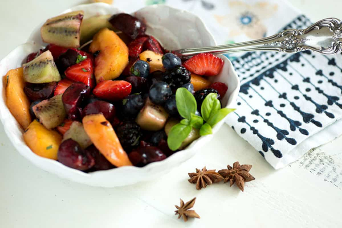 Star anise next to a bowl of fruit salad