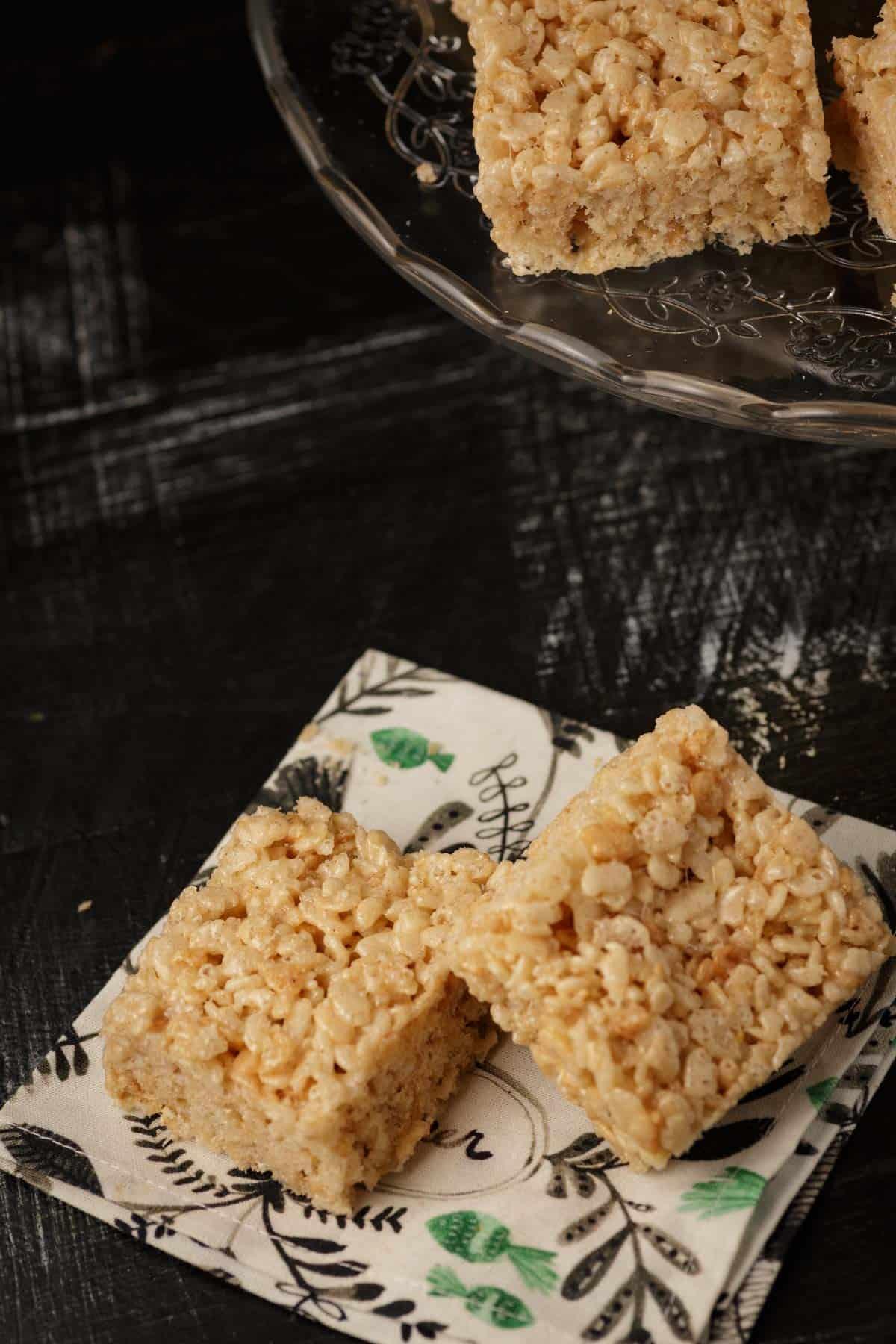 Two Rice Krispie treats on a cloth napkin.