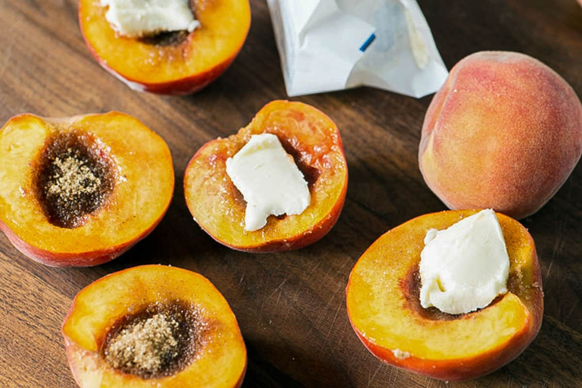 Peaches cut in half with butter on top.