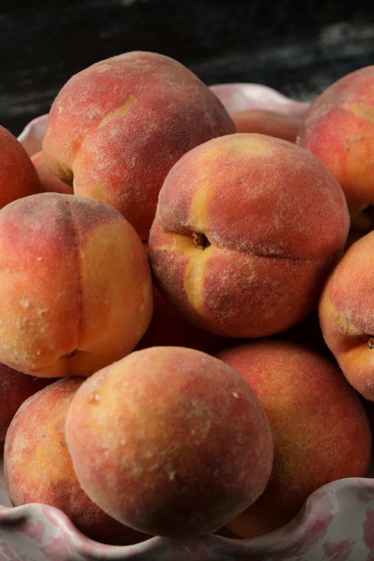 A ceramic bowl full of peaches.