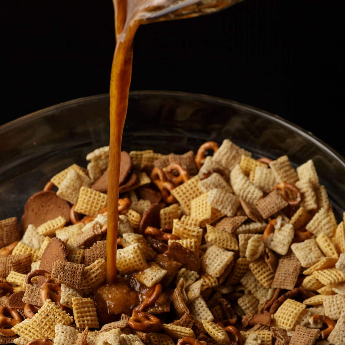 Seasoned butter being poured over a bowl of Chex mix