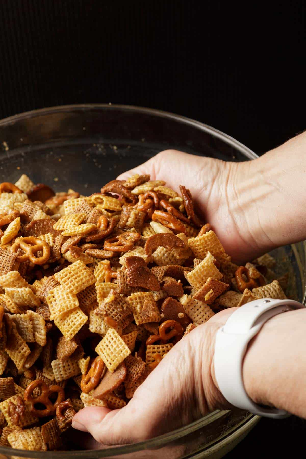 Party mix being combined with seasoned butter in a bowl.