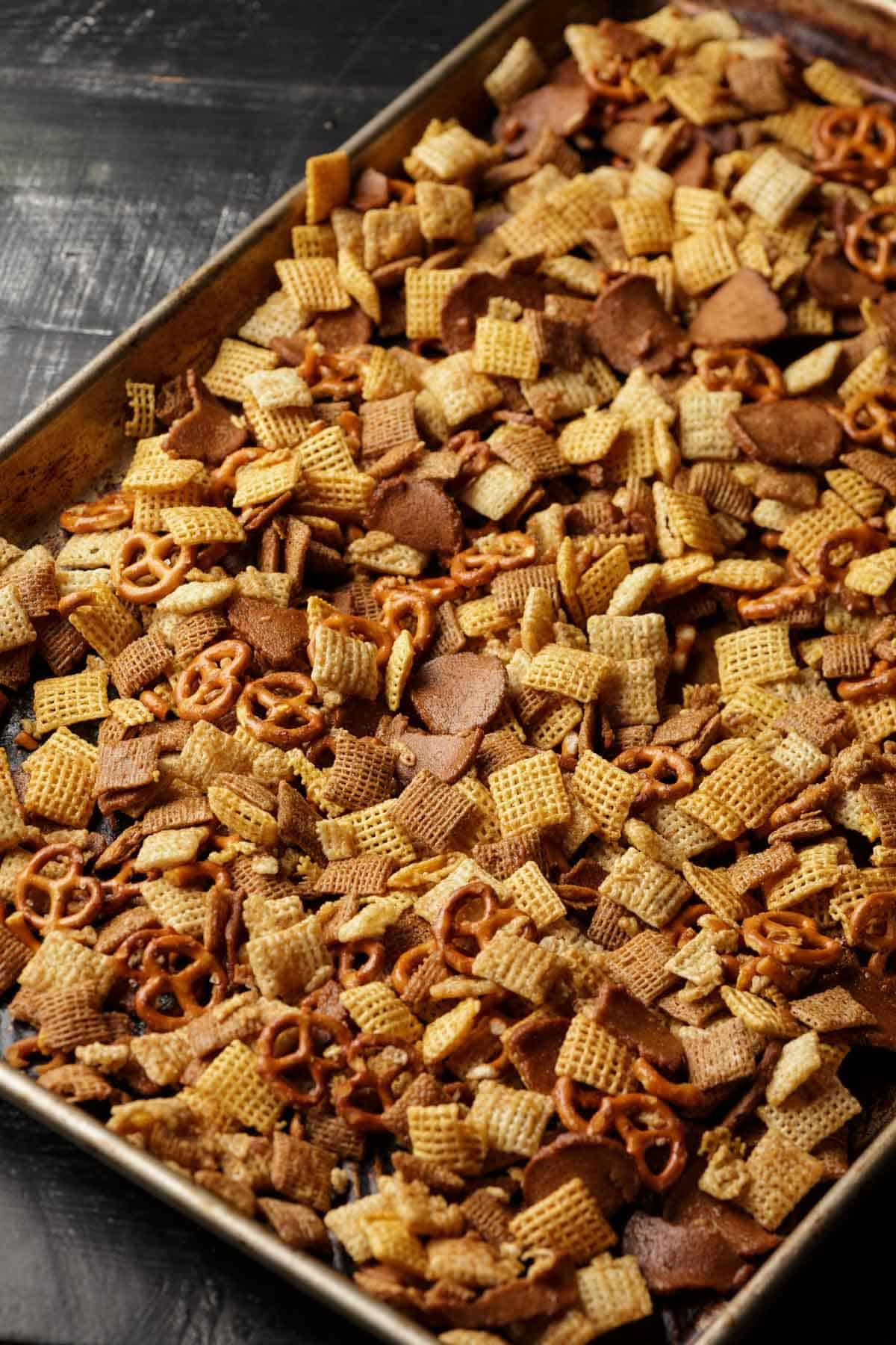 Homemade Chex mix spread out on a rimmed baking sheet.