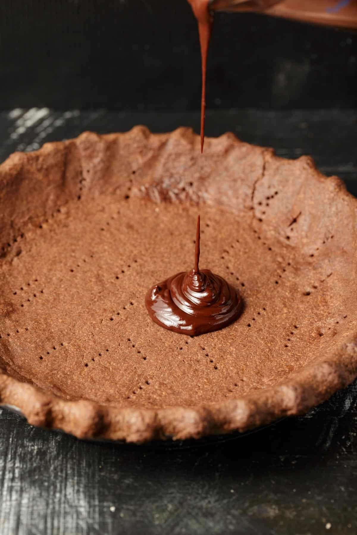 Chocolate ganache being poured into a chocolate pie crust.