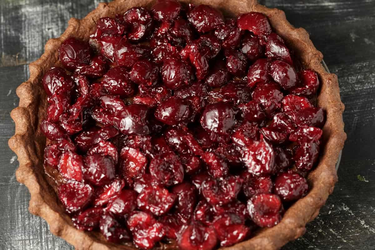 A black forest pie topped with cherries.