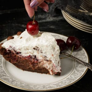 A slice of Black Forest pie with a cherry on top.