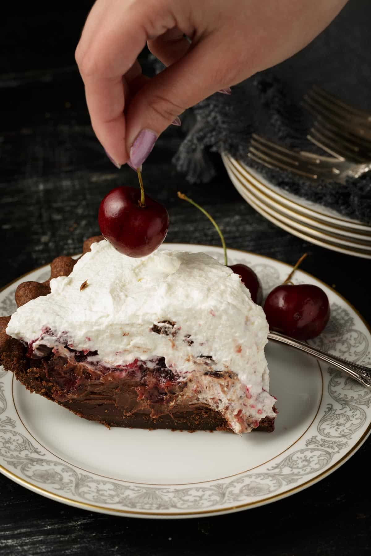A cherry being added to the top of a slice of black forest pie.