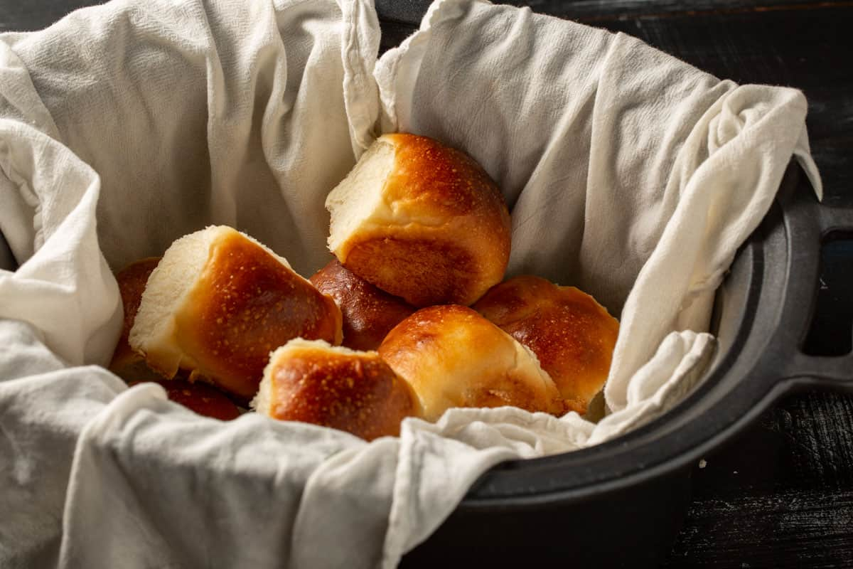 A slow cooker filled with yeast rolls.