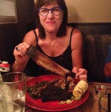 Barbara eating a rib at Bacon Brothers
